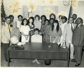 Pat Russell (seated, center) and her city council staff at Los Angeles City Hall, circa 1986-87. Yvette McFrazier is standing in back row, to the right of Russell (wearing black patterned top). Tavis Smiley is second from left.